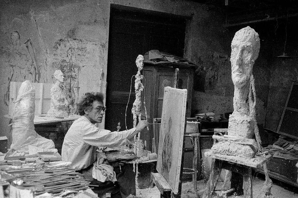 Giacometti beim Malen in seinem Atelier in Paris, daneben La Grande Tête, Paris, um 1957, Foto von Ernst Scheidegger (© 2018 Stiftung Ernst Scheidegger-Archiv, Zürich)