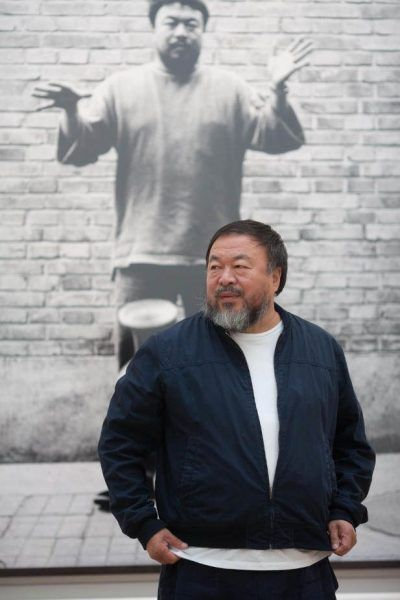 Ai Weiwei with one of his photographs from Dropping a Han Dynasty Urn, Royal Academy of Arts, 2015. Photo courtesy of Royal Academy of Arts, London. Photography © Dave Parry.