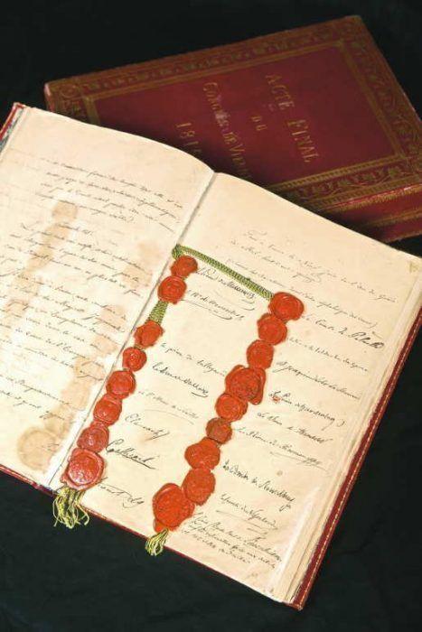 """Schlussakte des Wiener Kongresses (""""Österreichisches Exemplar""""), 1815, Papiercodex, Folien, in rotem Ledereinband mit Goldprägung und dazugehöriger, lederbespannter, mit grünem Samt gefütterter Holzkassette, Siebzehn aufgedrückte Lacksiegel an schwarz-gelber Seidenschnur, aufgeschlagen: 37,8 x 53,5 x 5 cm, Kassette: 40 x 28,5 x 9 cm (Österreichisches Staatsarchiv, Abteilung HHStA, Foto: © Andy Wenzel/BKA)."""