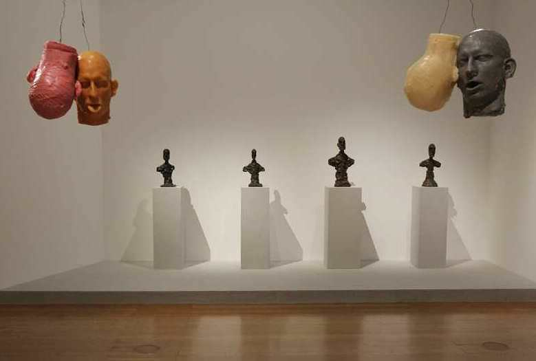Bruce Nauman, Ten Heads Circle/In and Out, 1990, Wachs, Draht, Zehn Köpfe, jeweils ca. 30,5 × 22,9 × 15,2 cm, Gesamtdurchmesser ca. 244 cm (Kunstmuseum Wolfsburg), dahinter: Alberto Giacometti, Büsten, Ausstellungsansicht Schirn 2016, Foto: Alexandra Matzner.