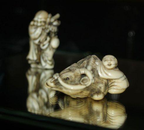 Zwei Netsuke: Im Vordergrund lehnt ein Hirtenknabe an einem Arbeitsochsen, Elfenbein,um 1780 und im Hintergrund unterhält der Mönch Hotei, einen Knaben mit einer Sanbaso-Handpuppe, Elfenbein, Osaka, ca. 1840 (Privatsammlung), Foto: Alexandra Matzner.