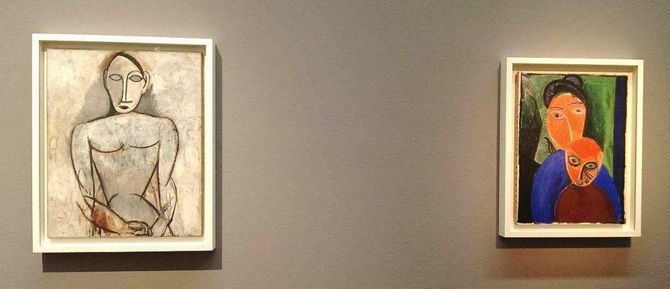 """Pablo Picasso, Frau mit gefalteten Händen, 1907, Musée national Picasso – Paris (links); Mutter mit Kind, 1907, Musée national Picasso – Paris (rechts), Ausstellungsansicht """"Fremde Götter. Faszination Afrika und Ozeanien"""" im Leopold Museum 2016/17, Foto: Alexandra Matzner © Bildrecht."""
