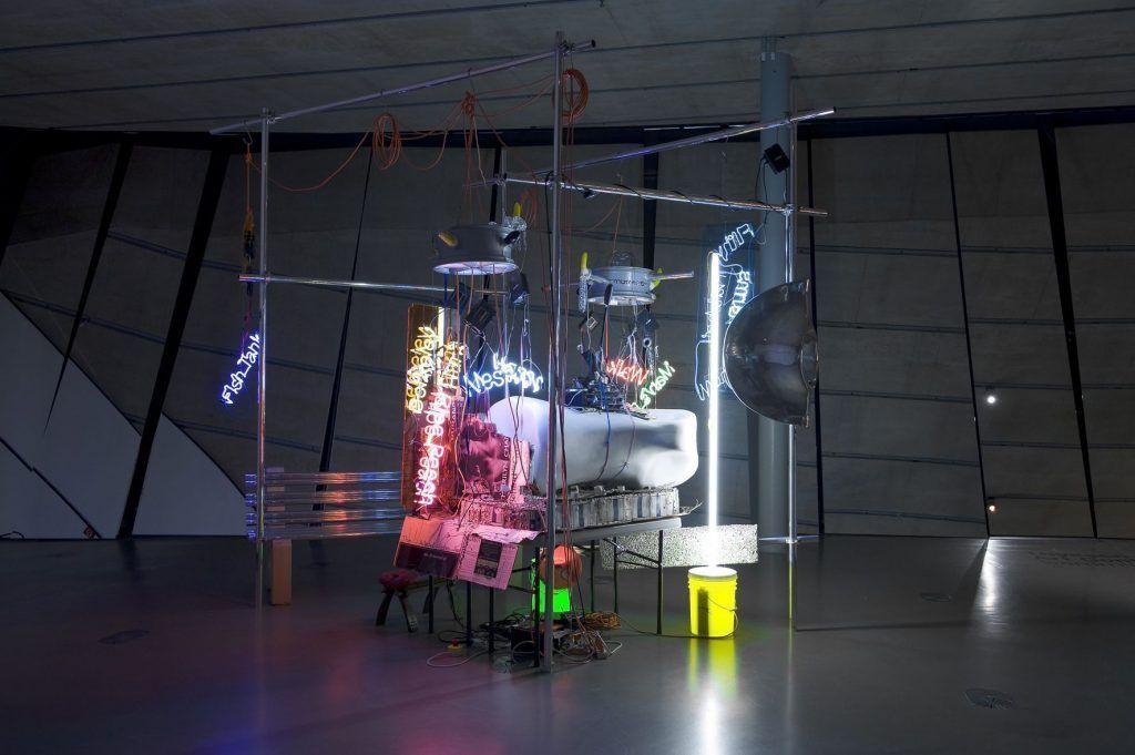 Jason Rhoades, Mi Saga, U Saga (Emmanuelle Saga), 2005, Multimedia-Installation: Emmanuelle Flatwork, Perfect World Bench (polierte Aluminiumrohre, Beton), Neon, Luster, Aluminiumrohre, Klemmen, Lautsprecher, Wailing Wall (Metalltisch, Fiberglas Kamelzehe, Plastik, PeaRoeFoam, Neon, Plexiglas, elektrische Leitung), Buch (1724 Birth of the Cunt, 2004), 360 × 370 × 420 cm, Thyssen-Bornemisza Art Contemporary, Wien, Foto © Landesmuseum Joanneum/ Niki Lackner.